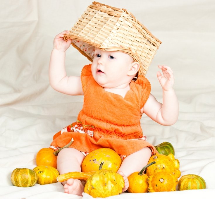Little baby girl playing with pumpkins and box